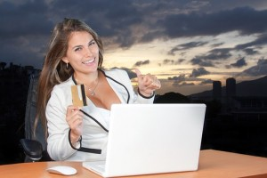 woman hand on a laptop holding card